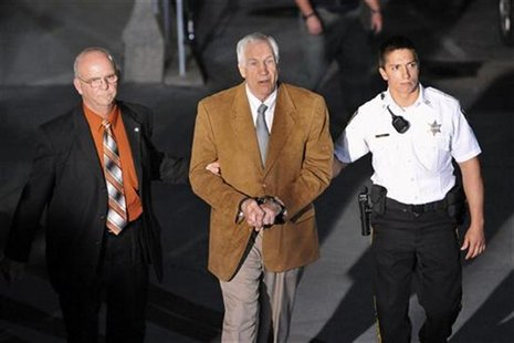 Former Penn State assistant football coach Jerry Sandusky leaves the Centre County Courthouse in handcuffs after his conviction in his child