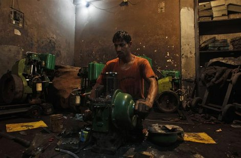 An employee works inside a power generator manufacturing workshop on the outskirts of New Delhi September 12, 2012. It is rough being an emp