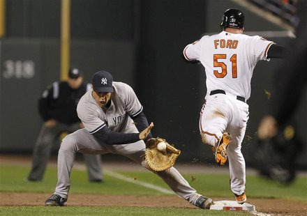 New York Yankees' Mark Teixeira (L) makes a catch to force out Baltimore Orioles' Lew Ford (R) at first base after Ford hit a sacrifice bunt