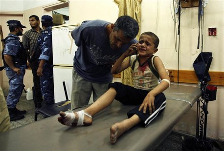 A wounded Palestinian boy speaks on the phone with his family following an Israeli air strike in Rafah camp in the southern Gaza Strip Octob