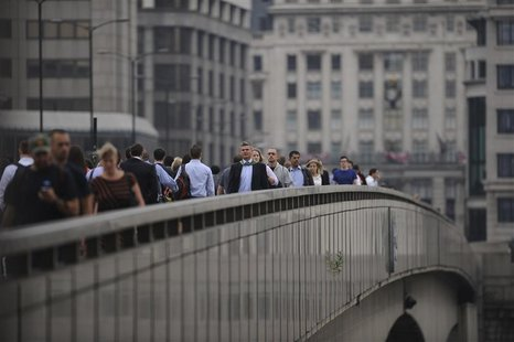 Commuters walk towards the financial district via London Bridge, three days after the end of the London 2012 Olympics August 15, 2012. REUTE