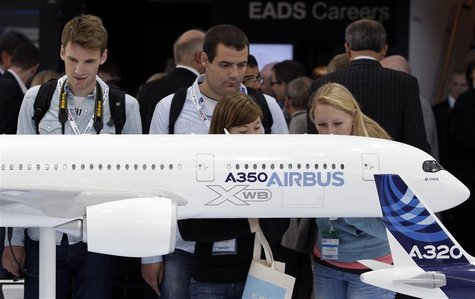 Visitors look at an A350 aircraft miniature at the EADS booth during the ILA Berlin Air Show in Selchow near Schoenefeld south of Berlin on