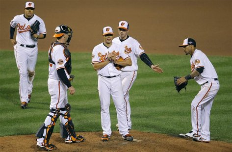 Baltimore Orioles starting pitcher Wei-Yin Chen is surrounded by his teammates as he waits to be relieved during the seventh inning against