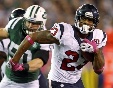 Houston Texans running back Arian Foster rushes against the New York Jets during the first quarter of their NFL football game in East Ruther