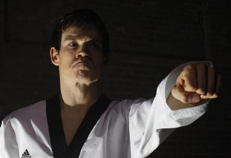 British Tae Kwon Do champion Aaron Cook poses for photos during a break in filming a promotional film at a location in central London, March