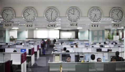 Workers are pictured beneath clocks displaying time zones in various parts of the world at an outsourcing centre in Bangalore February 29, 2