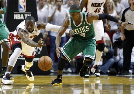 Miami Heat's Dwyane Wade (L) fights for a loose ball with Boston Celtics' Rajon Rondo in the third quarter during Game 7 of their Eastern Co