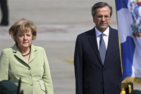 Germany's Chancellor Angela Merkel is welcomed by Greece's Prime Minister Antonis Samaras (R) upon arrival at Eleftherios Venizelos airport