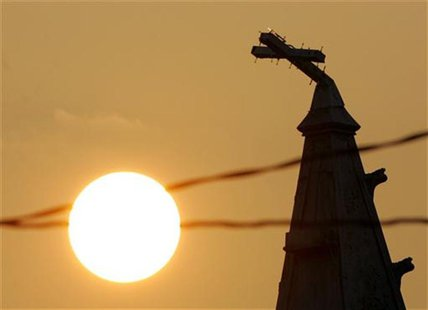 A broken cross is seen on the top of a church in New Orleans September 18, 2005. REUTERS/Carlos Barria
