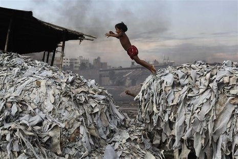 A child jumps on the waste products that are used to make poultry feed as she plays in a tannery at Hazaribagh in Dhaka October 9, 2012. REU
