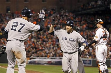 New York Yankees' Russell Martin (C) is congratulated by his teammate Raul Ibanez (L) after Martin hit a solo home run in the ninth inning a