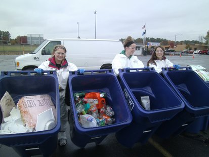 Mosinee High School Green Team members Emily Babcock (left) Hannah Hill (center) and Kortney Marshall (right) showing some of the recyclable materials removed from the garbage.
