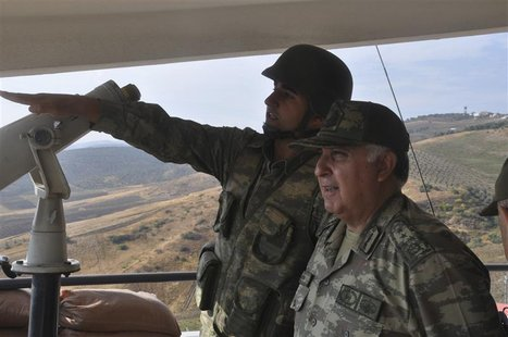 Turkey's Chief of General Staff Necdet Ozel (R) receives information during his visit at a border outpost on the Turkish-Syrian border in Ha