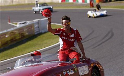 Ferrari Formula One driver Fernando Alonso of Spain waves during the driver's parade of the Japanese F1 Grand Prix at the Suzuka circuit Oct