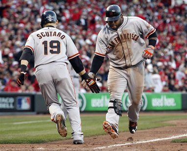 San Francisco Giants third baseman Pablo Sandoval (R) slaps hands with teammate Marco Scutaro after driving him home with a seventh inning t