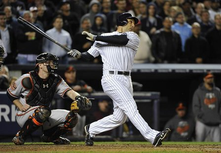 New York Yankees' Raul Ibanez hits a solo home run in front of Baltimore Orioles catcher Matt Wieters during the ninth inning in Game 3 of t