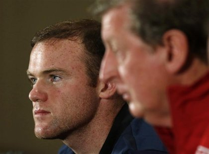 England's national soccer team manager Roy Hodgson (R) and captain Wayne Rooney attend a media conference at the team's hotel in Watford, no