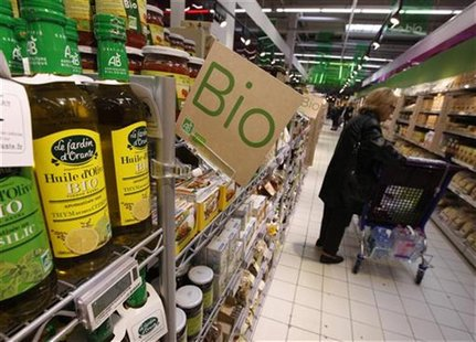 A customers buys organic products in the Bio foods section at Carrefour Planet supermarket in Nice Lingostiere November 29, 2011. REUTERS/Er
