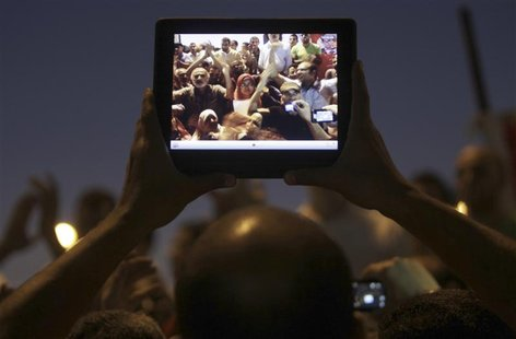 Egyptian protesters are pictured on a tablet device during a protest against general prosecutor Abdel Maguid Mahmoud and the Mubarak regime