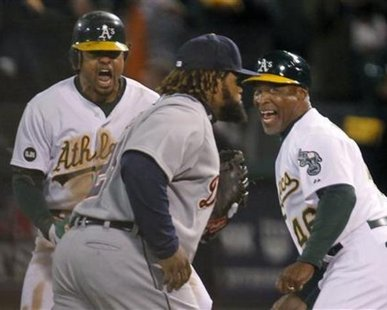 YOU'RE GOING DOWN, PRINCE! Oakland Athletics center fielder Coco Crisp (L) and first base coach Tye Waller celebrate Crisp's game winning RBI in the 9th inning as Detroit Tigers first baseman Prince Fielder (28) walks off the field during Game 4 of their MLB ALDS playoff baseball series in Oakland, California October 10, 2012. REUTERS/Robert Galbraith
