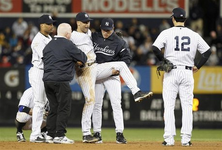 New York Yankees third baseman Eric Chavez (12) looks on as shortstop Derek Jeter is carried off the field by trainer Steve Donohue (2nd fro
