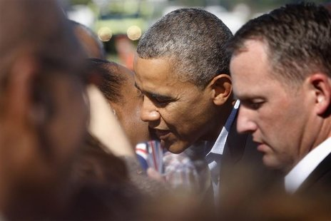 U.S. President Barack Obama gets a kiss from a woman in the crowd as he arrives at Newport News/Williamsburg International Airport in Willia