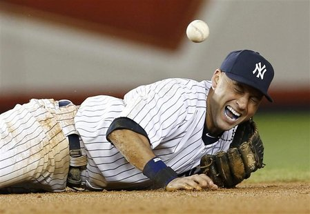 New York Yankees shortstop Derek Jeter screams as he injures himself fielding a ball hit by Detroit Tigers' Jhonny Peralta during the 12th i