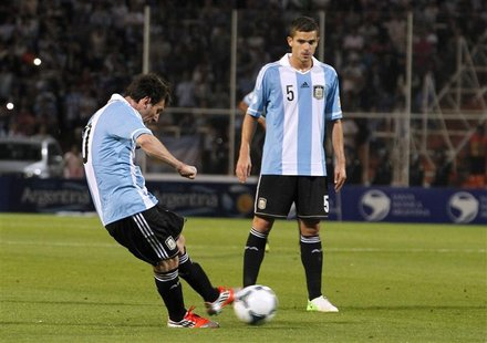 Argentina's Lionel Messi (L) kicks the ball to score his second goal against Uruguay as his teammate Fernando Gago looks on during their 201