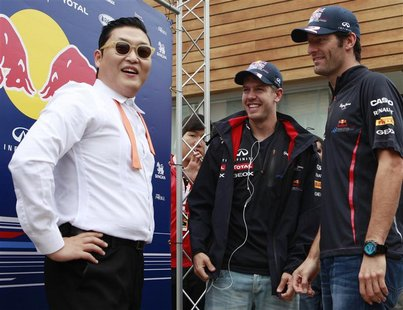 South Korean singer Psy (L), Red Bull Formula One driver Sebastian Vettel (C) of Germany and teammate Mark Webber of Australia talk after pe