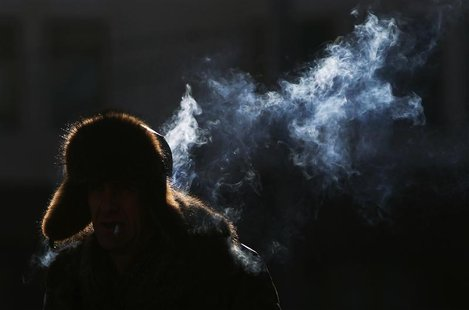 A man smokes a cigarette as he walks through a shaft of sunlight in temperatures, about minus 15 degrees Celsius (5 degrees Fahrenheit) in c