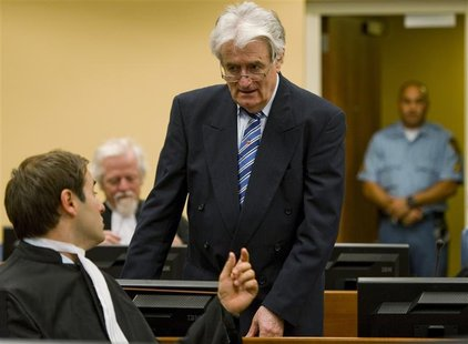 Former Bosnian Serb leader Radovan Karadzic talks to member of his legal team Marko Sladojevic in the courtroom on the first day of his defe