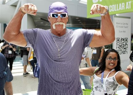 Wrestler Hulk Hogan poses for a photo as a fan also poses as he walks in the Los Angeles Convention Center while on site to promote Majesco