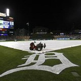 Groundskeeping equipment and the tarp cover the infield at Coamerica Park during a rain delay prior to the start of Game 4 of the ALCS baseball playoffs between the Detroit Tigers and the New York Yankees in Detroit, October 17, 2012. Game 4 was later postponed until Thursday because of the continued threat of inclement weather. REUTERS/Jessica Rinaldi