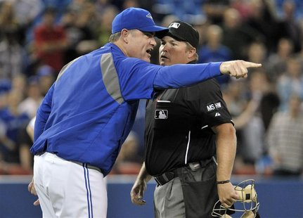 Former Toronto Blue Jays manager John Farrell (L) argues a call with home plate umpire Marvin Hudson during the 10th inning of their MLB Ame
