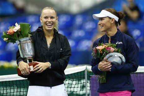 Denmark's Caroline Wozniacki holds her trophy after defeating Australia's Samantha Stosur (R) in the women's singles final at the Kremlin cu