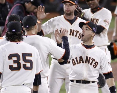 San Francisco Giants second baseman Marco Scutaro (R) celebrates defeating the St. Louis Cardinals with teammate Hunter Pence at the conclus