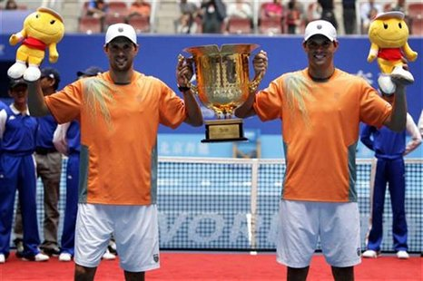 Bob Bryan and Mike Bryan of the U.S. hold the trophy after winning the men's doubles final against Argentina's Carlos Berlocq and Uzbekistan
