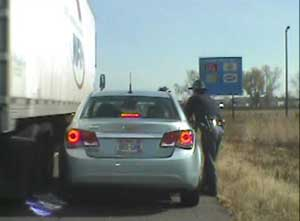 Trooper Charles Hotvedt narrowly escapes being hit by a passing semi truck while he was conducting a routine traffic stop on I-94 in Eau Claire County, October 15, 2012 (provided by WisDOT)