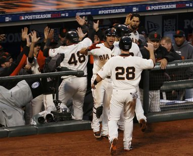 San Francisco Giants catcher Buster Posey (28) is welcomed back to the dugout after scoring against the St. Louis Cardinals in the third inn