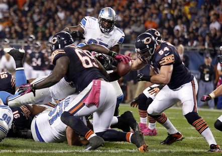 Detroit Lions Joique Bell fumbles the ball as Chicago Bears middle linebacker Brian Urlacher (54) and defensive tackle Henry Melton (69) mak