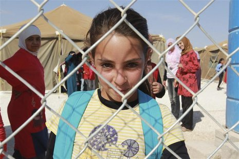 A Syrian refugee girl looks out from behind a fence as she attends school at the Zaatari refugee camp in the Jordanian city of Mafraq, near