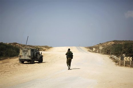 An Israeli soldier walks beside a military vehicle near the border with the northern Gaza Strip October 22, 2012. REUTERS/Amir Cohen
