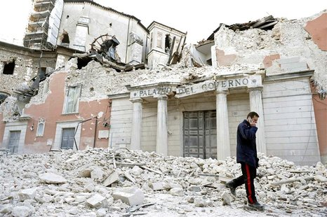 An Italian military carabinieri walks on debris past destroyed buildings after an earthquake, in downtown Aquila, in this April 6, 2009 file