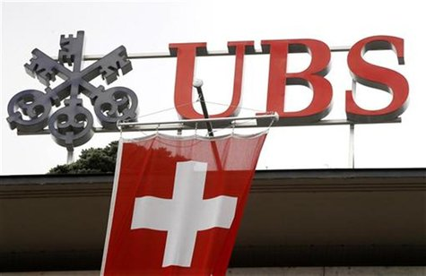 A Switzerland national flag flies in front of the logo of Swiss bank UBS at the company's headquarters in Zurich April 13, 2012. REUTERS/Arn