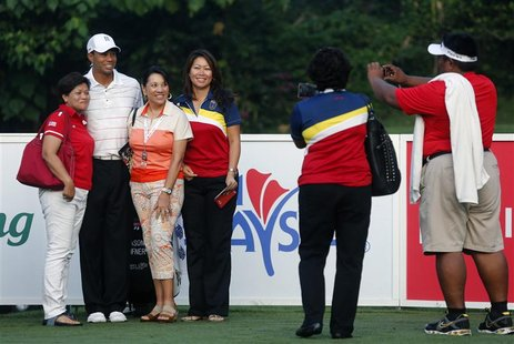 Fans pose wih Tiger Woods (2nd L) of the U.S. as he plays in the Pro-Am ahead of the Malaysia's Asia Pacific Classic golf tournament in Kual