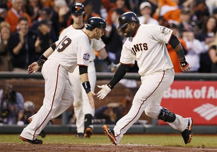 San Francisco Giants' Pablo Sandoval (R) celebrates with teammate Marco Scutaro after hitting a two RBI home run against the Detroit Tigers