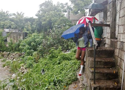 Jamaicans shelter themselves from the rain of approaching Hurricane Sandy as they walk along Sandy Park Gully in Kingston October 24, 2012.