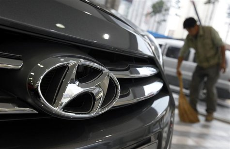 The logo of Hyundai Motor is seen on the on a car as a worker sweeps a floor at a Hyundai dealership in Seoul October 25, 2012. REUTERS/Kim