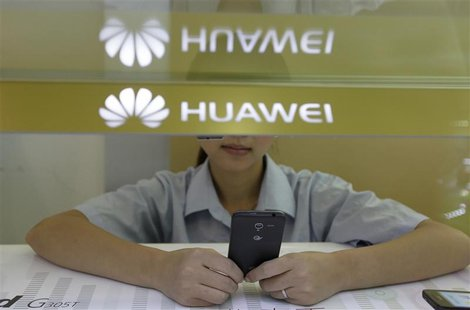 A sales assistant looks at her mobile phone as she waits for customers behind a counter at a Huawei booth in Wuhan, Hubei province, October