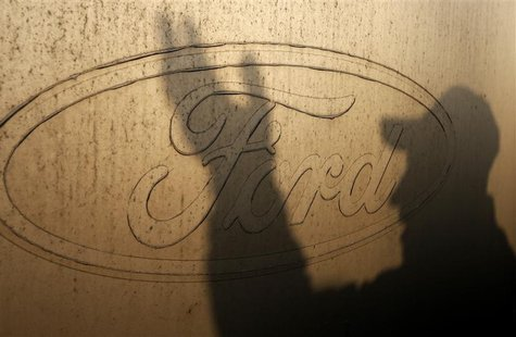 The shadow of a worker is seen on the logo of Ford Motor Co at the company's assembly plant after an emergency meeting with the plant manage